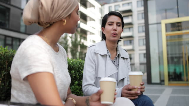 female arabic friends having coffee together outdoors - shopping bag stock videos & royalty-free footage