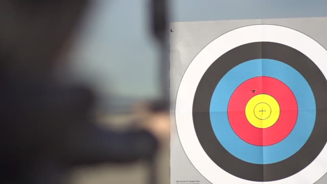 stockvideo's en b-roll-footage met a female archer shooting targets with her bow and arrow.  - slow motion - filmed at 480 fps - richten
