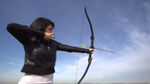 a female archer shooting targets with her bow and arrow.  - slow motion - filmed at 480 fps - bow and arrow stock videos and b-roll footage