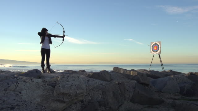 a female archer shooting targets with her bow and arrow.  - super slow motion - filmed at 240 fps - bull's eye stock videos and b-roll footage