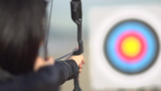 a female archer shooting targets with her bow and arrow.  - super slow motion - filmed at 240 fps - sports target stock videos and b-roll footage