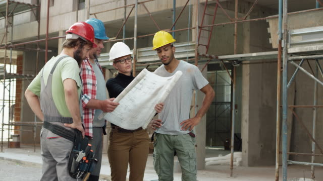 vídeos de stock e filmes b-roll de female architect, a foreman and two construction workers looking at the plan outside at the construction site and pointing at the building to check the progress - gola alta