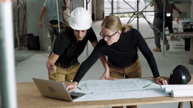 female architect and female construction coordinator checking the plans at the construction site - solo donne video stock e b–roll