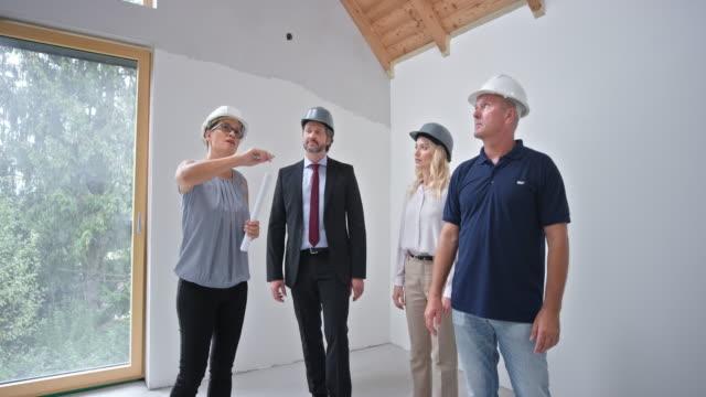 vidéos et rushes de architecte féminin et superviseur masculin de construction parlant aux investisseurs dans leur future maison - expliquer