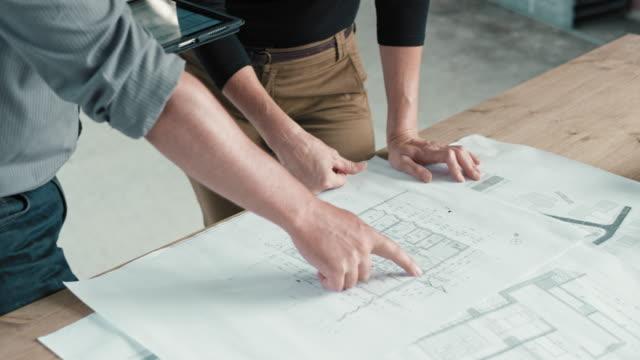 vídeos y material grabado en eventos de stock de hombre y mujer arquitecto ingeniero comparando planes sobre la mesa con los de la tableta digital en el sitio de construcción - cianotipo plano
