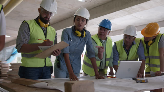 female architect assigning tasks to her team at a construction site pointing to the blueprint while talking - inspector stock videos & royalty-free footage
