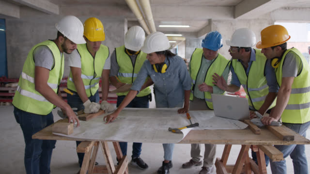female architect at a construction site during a meeting with the team talking while pointing at a blueprint - foreman stock videos & royalty-free footage