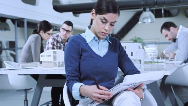 TU Female architect checking interior designs in meeting room