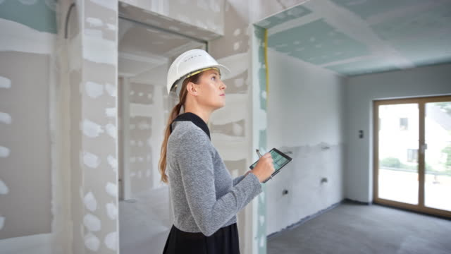 female architect comparing the progress with the plans on her digital tablet inside the building - inspector stock videos & royalty-free footage