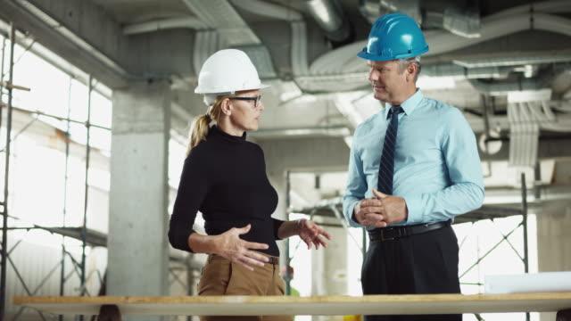 vidéos et rushes de architecte ds femmes discutant les plans sur le site avec le gestionnaire de projet mâle - cravate