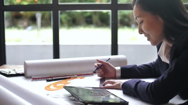 architektin ausarbeitung auf blaupausen im büro - architekt stock-videos und b-roll-filmmaterial