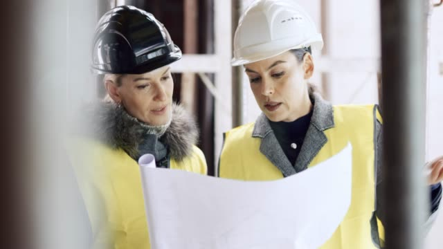 Female architect explaining plan details to the female investor on the construction site