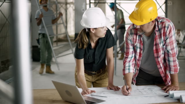 Female architect explaining the foreman details of the plan by checking on the laptop and showing him on the plan sheet