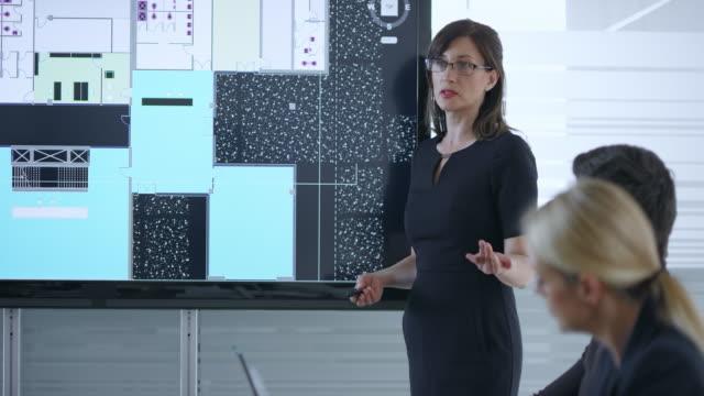 vidéos et rushes de femme architecte donnant une présentation des plans du projet à l'aide de l'écran dans la salle de réunion - montre