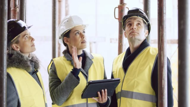 female architect holding a tablet and explaining details of the construction plan to the male and female investor - architetto video stock e b–roll