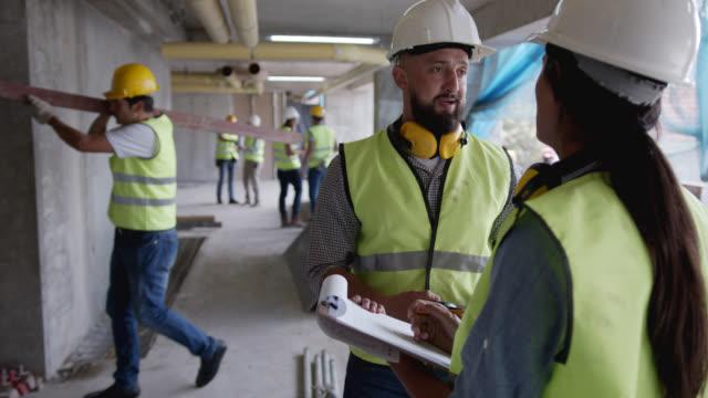 建設現場でエンジニアと話し合いながらクリップボードに置いて文書を見る女性建築家 - 土木技師点の映像素材/bロール
