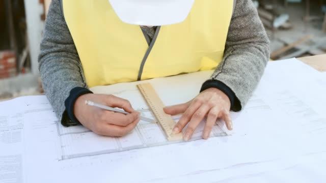 Architektin, die Änderungen an die Baupläne auf der Baustelle