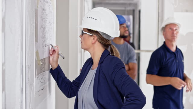 ld female architect making changes to the plan hanging on the board at the building site - caposquadra video stock e b–roll