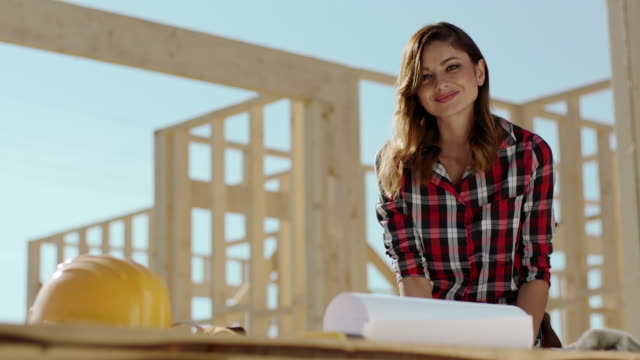 Female architect on construction site looking at blueprints