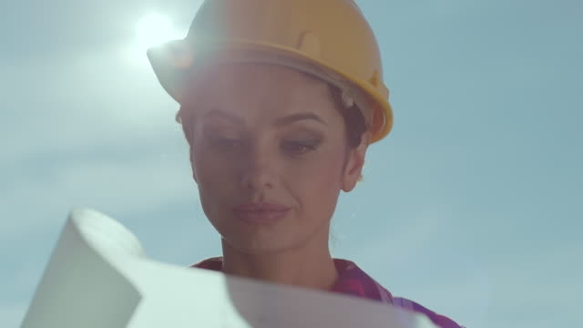 female architect on construction site looking at blueprints - construction frame stock videos & royalty-free footage