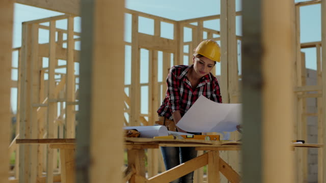 Female architect on construction site reviewing blueprints
