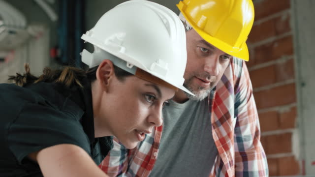 Female architect showing a foreman details on the laptop at the construction site