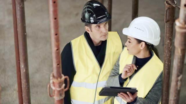 Female architect showing the male investor how a plan detail will be implemented into the building site