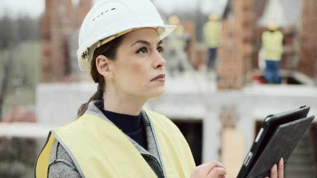 female architect standing at the construction site and checking the plans on the digital tablet - construction site stock videos & royalty-free footage