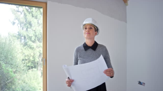 female architect standing in a room in the unfinished building and checking the progress - business casual stock videos & royalty-free footage