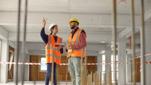 female architect talking to a male construction worker and explaining a construction detail about the build - hard hat stock videos & royalty-free footage