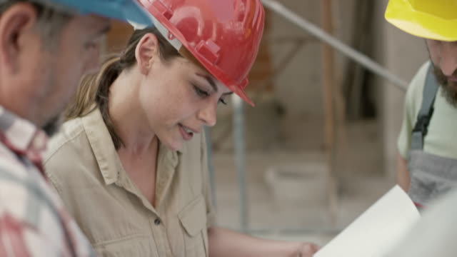 Female architect talking to the construction workers and pointing out details on the plan she is holding