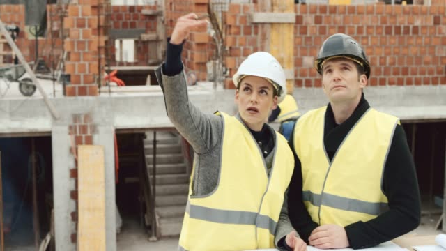 female architect talking to the male investor standing at the construction site and drawing details onto the plan for him - blueprint stock videos & royalty-free footage