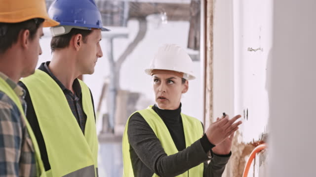 ds female architect talking to the site manager and a foreman - safety stock videos & royalty-free footage