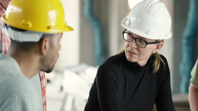 Female architect talking to workers at the construction site, discussing the plans set on the table