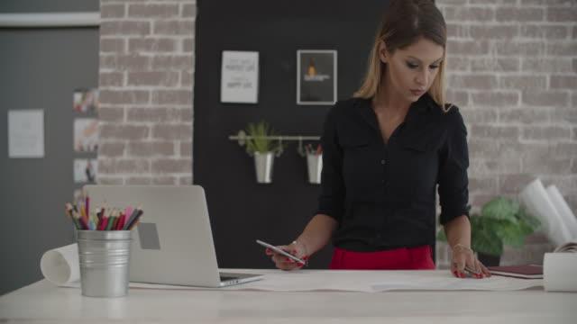 vídeos y material grabado en eventos de stock de hembra arquitecto trabajando en su oficina. - profesional de diseño
