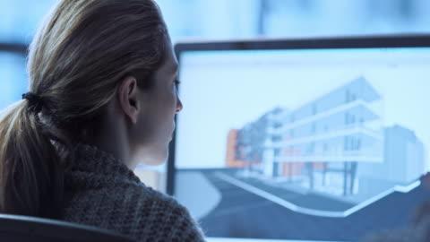 tu kvinnliga arkitekt arbetar på en virtuell modell - planering bildbanksvideor och videomaterial från bakom kulisserna