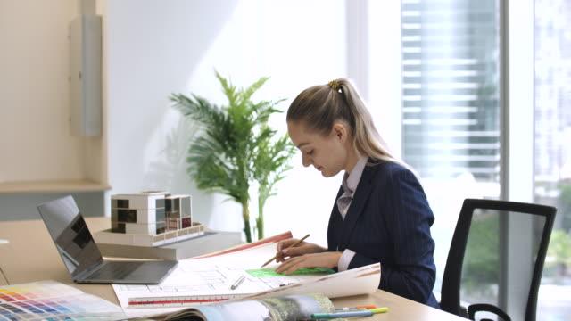 机の上で働く女性建築家 - 図面点の映像素材/bロール