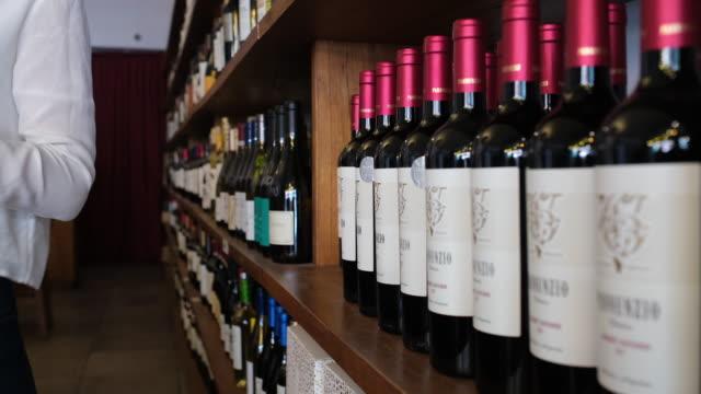 female arranging wine bottles on shelf at wine shop - selling stock videos & royalty-free footage