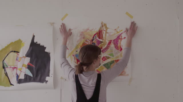 stockvideo's en b-roll-footage met female artist hangs painting on wall and takes and send photos by using phone. - hangen