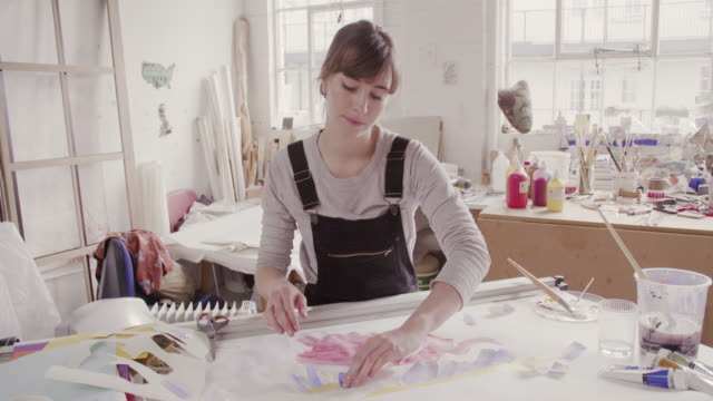 female artist is cutting shapes out of paper and places it on artwork. - bib overalls stock videos and b-roll footage