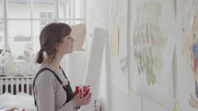 Female artist looks at abstract paintings on studio wall.