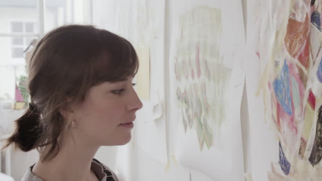 female artist looks at paintings hanging on wall art studio. - content stock videos and b-roll footage