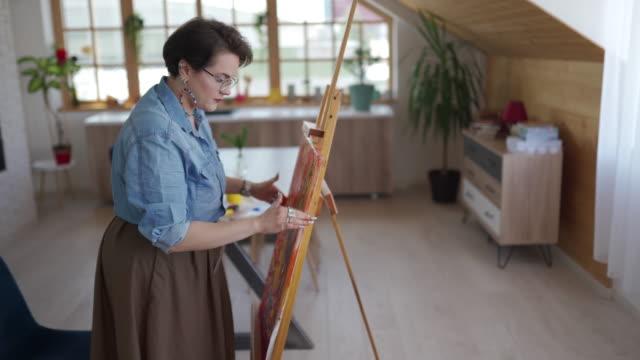 vídeos y material grabado en eventos de stock de artista femenina que duele con los dedos en el lienzo en el taller - sólo mujeres jóvenes