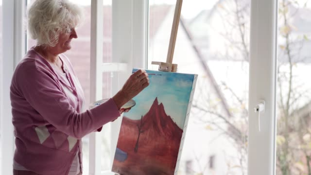 female artist painting landscape at the studio - pittore video stock e b–roll