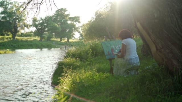 vídeos y material grabado en eventos de stock de artista femenina pintando al aire libre - fémina