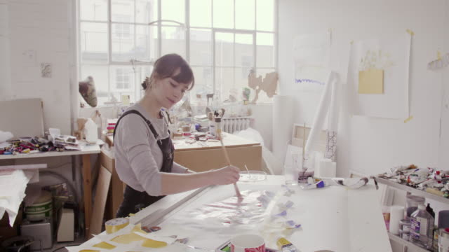 Female artist paints abstract painting in studio.