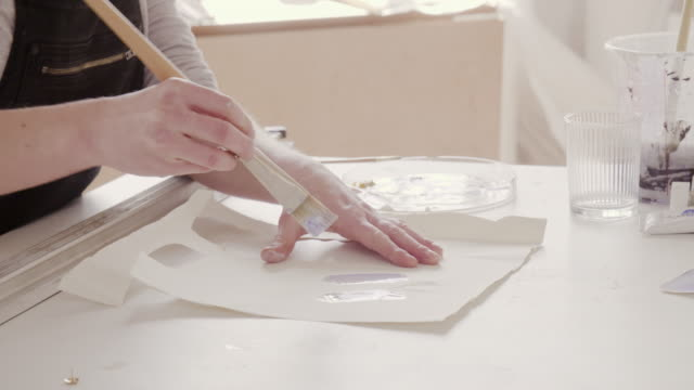 Female artist paints on paper in art studio.