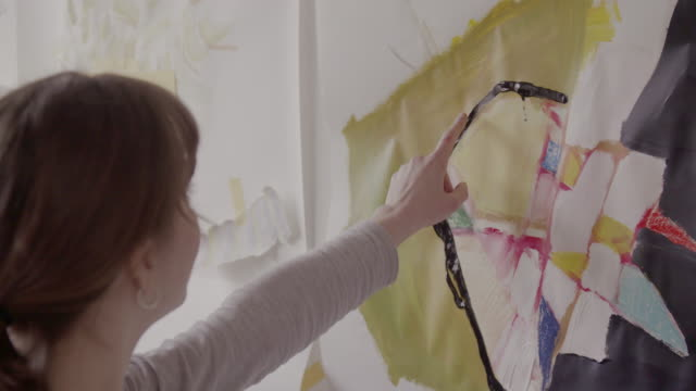 female artist points to painting, while discussing abstract art. - admiration stock videos and b-roll footage