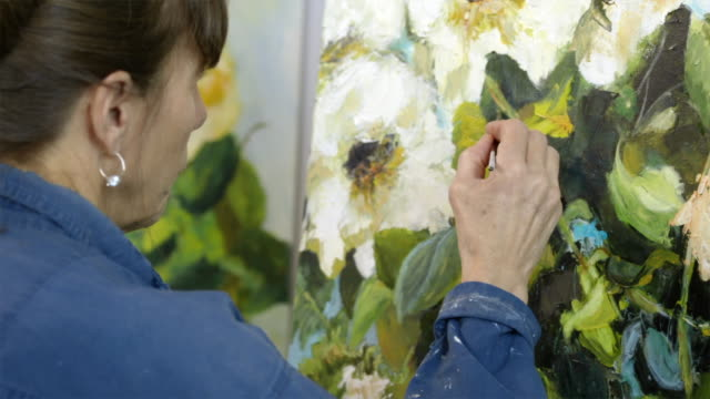 Female artist producing oil painting of flowers on canvas