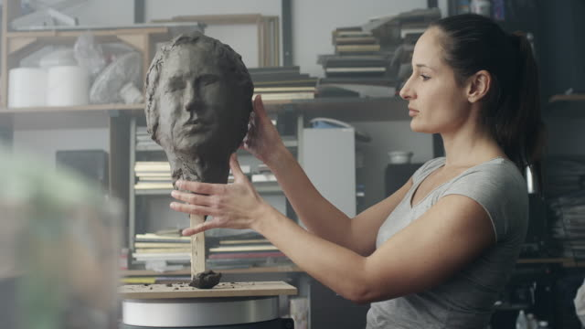 Female artist sculpting face